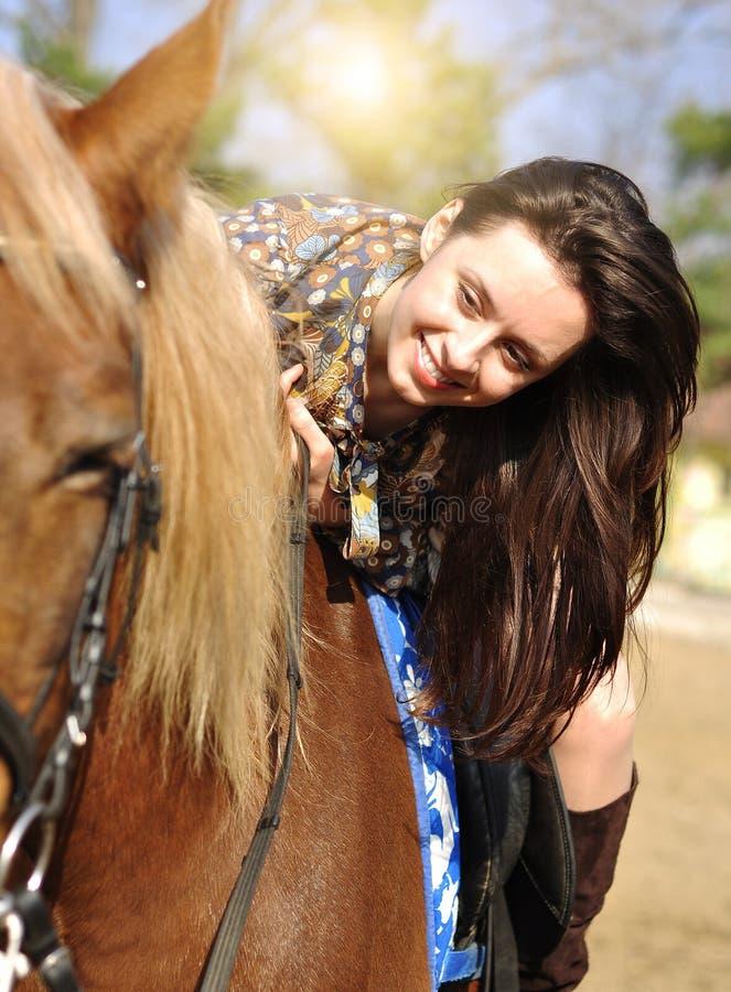 Jeune jolie brune montant et caressant son cheval extérieur photos stock