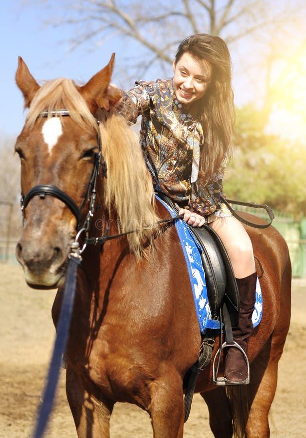 Jeune jolie brune montant et caressant son cheval extérieur images libres de droits