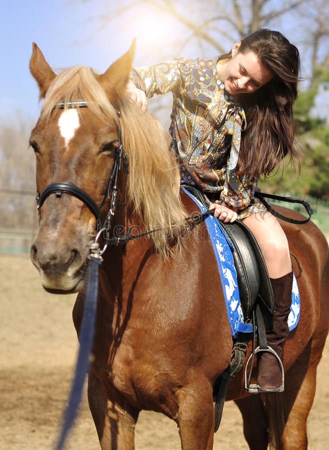 Jeune jolie brune montant et caressant son cheval extérieur image libre de droits