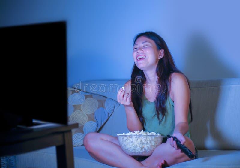 Jeune jolie et heureuse femme coréenne asiatique s'asseyant au popc de fin de nuit de observation de consommation de comédie de t photos stock
