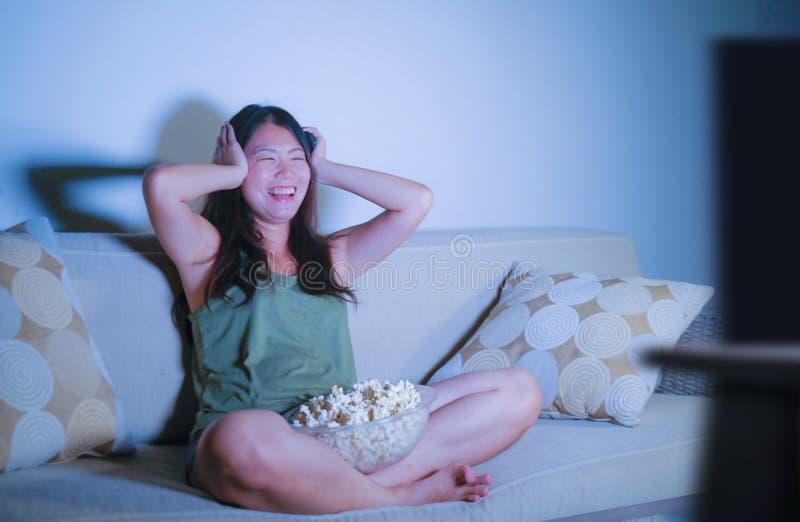 Jeune jolie et heureuse femme coréenne asiatique s'asseyant au popc de fin de nuit de observation de consommation de comédie de t photographie stock libre de droits