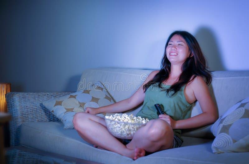 Jeune jolie et heureuse femme coréenne asiatique s'asseyant au popc de fin de nuit de observation de consommation de comédie de t photo stock