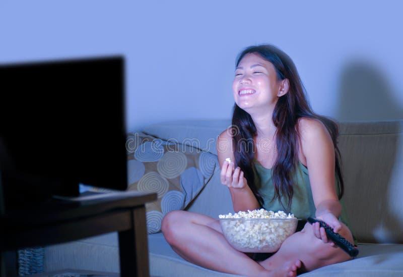 Jeune jolie et heureuse femme coréenne asiatique s'asseyant au popc de fin de nuit de observation de consommation de comédie de t image stock