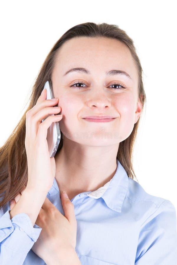 Jeune jolie femme à l'aide d'un téléphone portable sur le fond blanc photographie stock