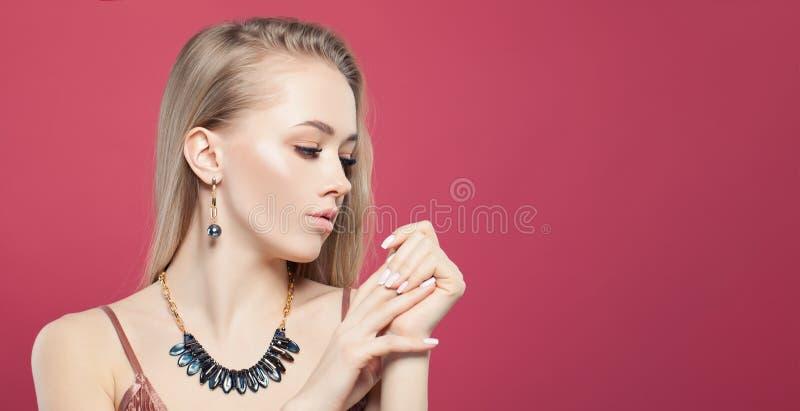 Jeune jolie femme blonde avec les boucles d'oreille et les colliers à chaînes d'or avec la pierre d'hématite sur le fond rose lum image libre de droits