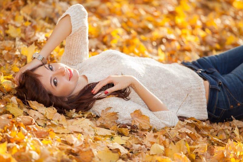 Jeune jolie femme détendant en parc d'automne Scène de nature de beauté avec le fond coloré de feuillage, les arbres jaunes et le images stock