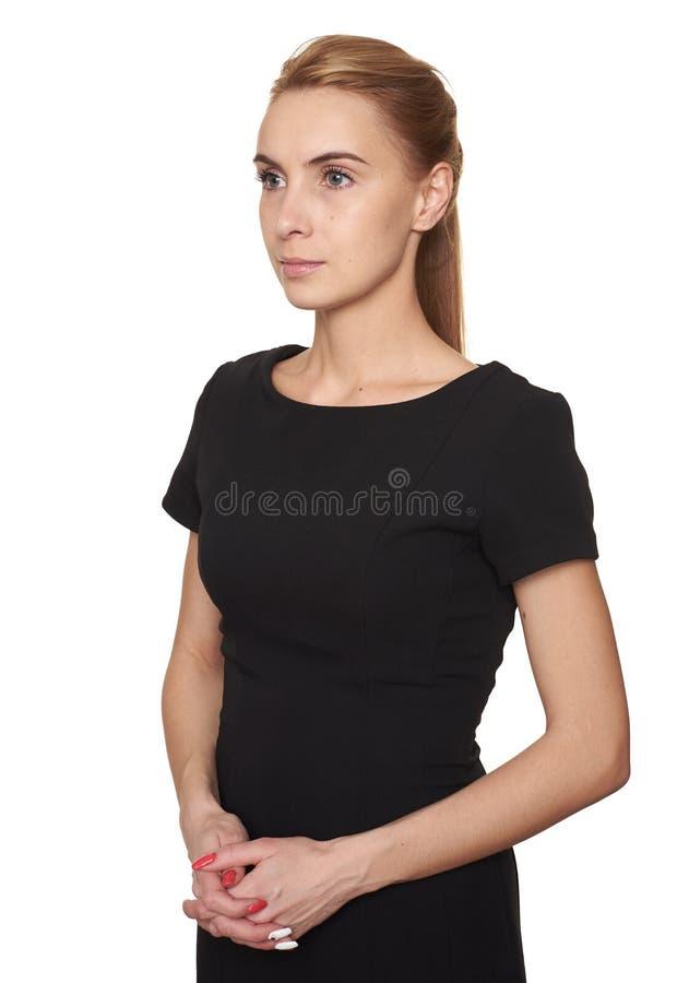 Jeune jolie femme dans la robe noire regardant loin d'isolement photographie stock libre de droits