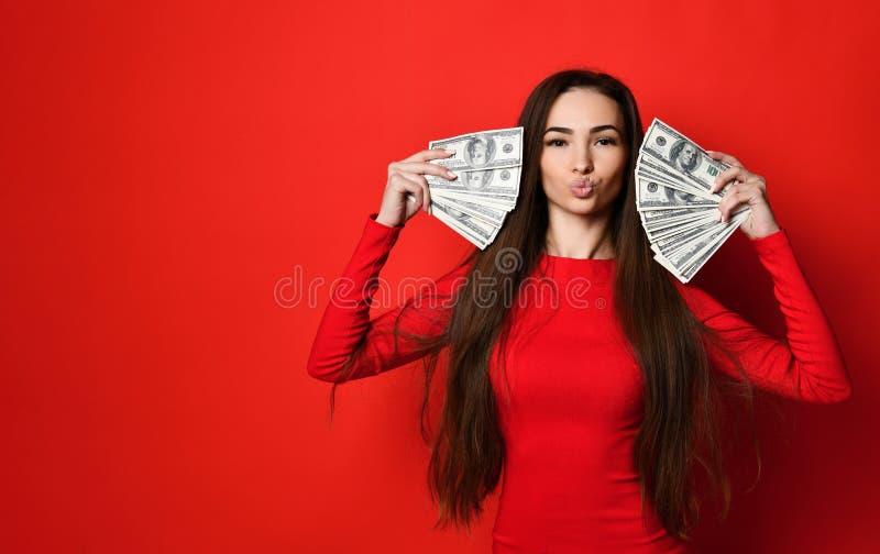 Jeune jolie femme dans la robe rouge se cachant derrière le groupe de billets de banque d'argent photos libres de droits