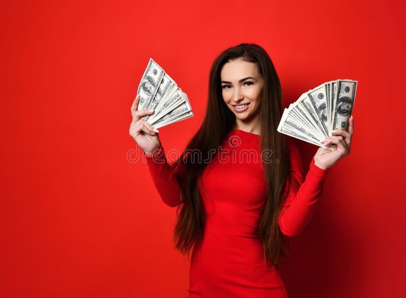 Jeune jolie femme dans la robe rouge se cachant derrière le groupe de billets de banque d'argent images libres de droits