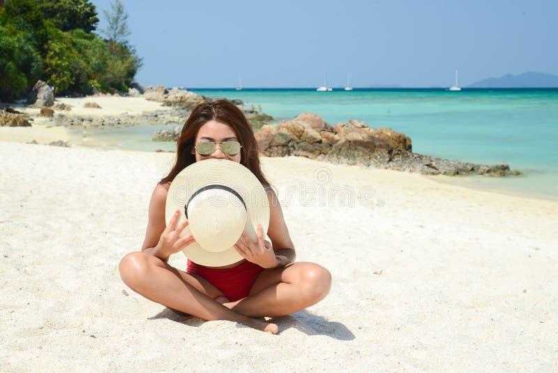 Jeune jolie femme dans le bikini rouge détendant à la plage de mer de turquoise avec l'air frais d'été photo libre de droits
