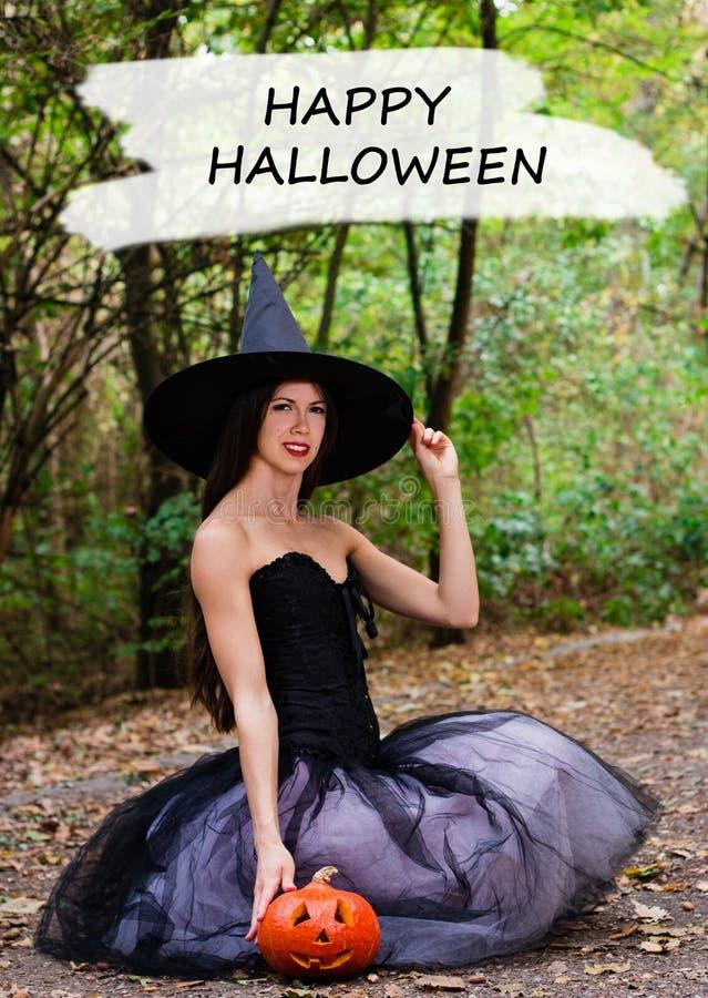 Jeune jolie femme dans le chapeau du ` s de sorcière tenant le cric de potiron de Halloween images libres de droits