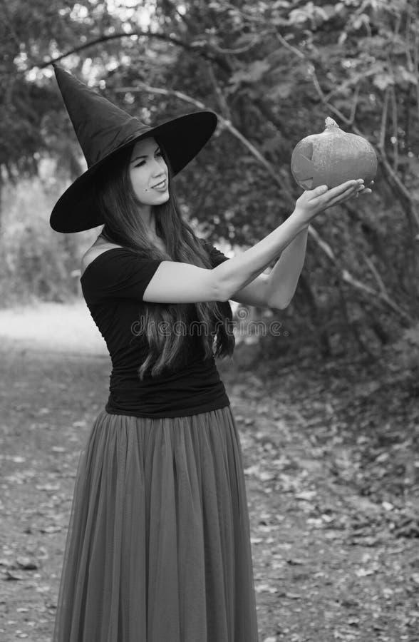 Jeune jolie femme dans le chapeau du ` s de sorcière tenant le cric de potiron de Halloween photo libre de droits