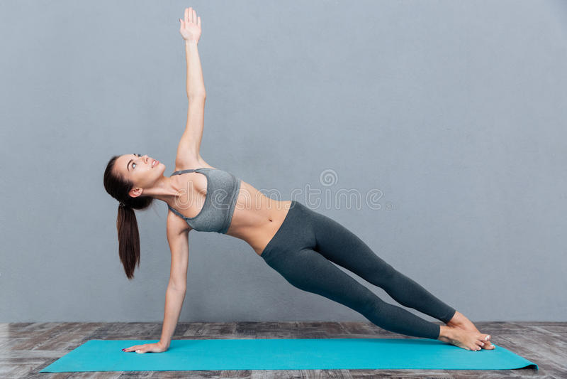 Jeune jolie femme dans le yoga de pratique de vêtements de sport noirs photographie stock