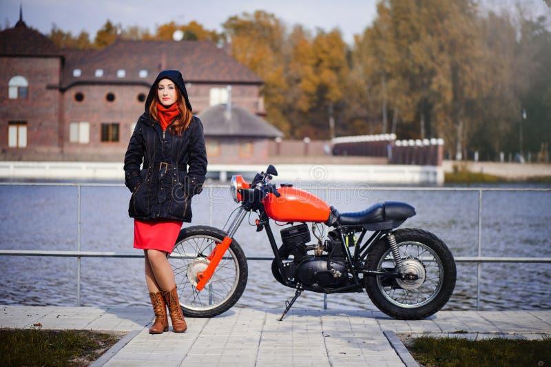 Jeune jolie femme dans un capot pendant la saison froide contre une moto rouge et une forêt jaune, des cheveux rouges et une écha photo libre de droits
