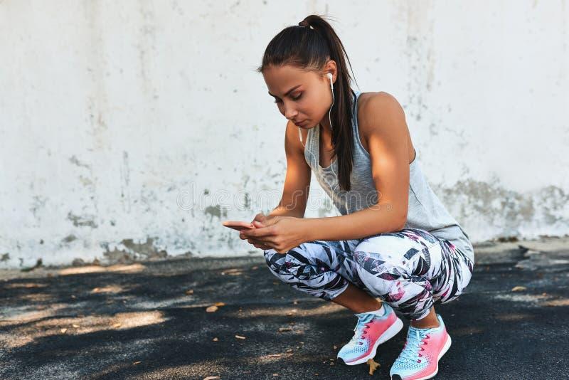 Jeune jolie femme de forme physique écoutant la musique sur des écouteurs pendant un extérieur de coupure contre le mur en béton  photo stock