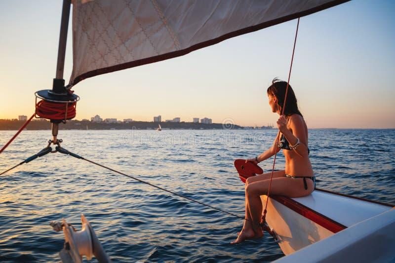 Jeune jolie femme de sourire au yacht de luxe en mer, regardant en avant, temps de soirée de coucher du soleil photos libres de droits