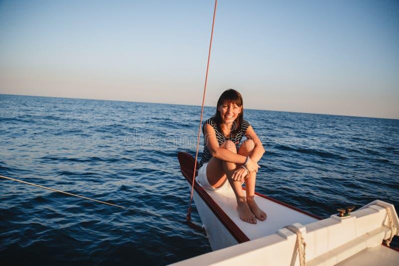 Jeune jolie femme de sourire dans la chemise rayée et les shorts blancs au yacht de luxe en mer, coucher du soleil images libres de droits