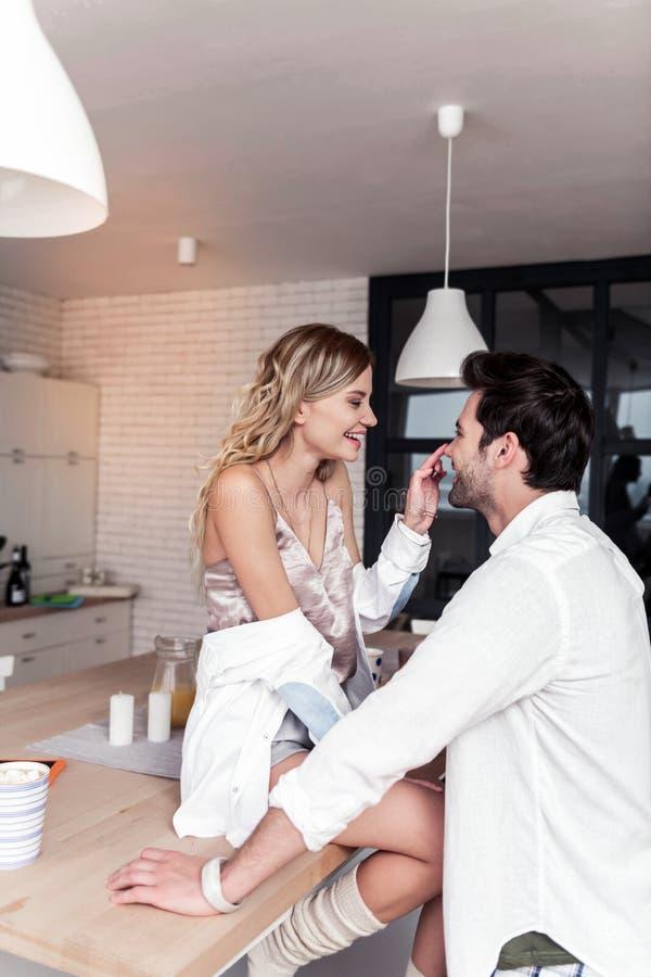 Jeune jolie femme de sourire dans une chemise blanche ayant l'amusement avec son mari photos stock