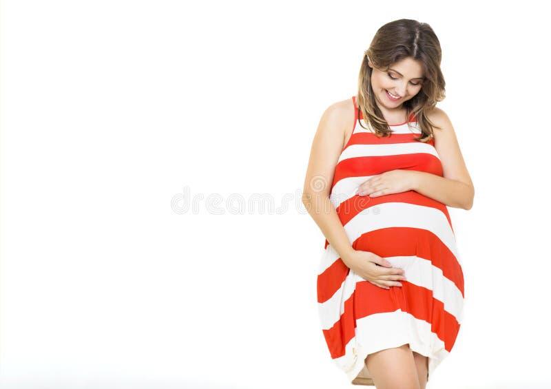 Jeune jolie femme enceinte de sourire sur le fond blanc photo libre de droits