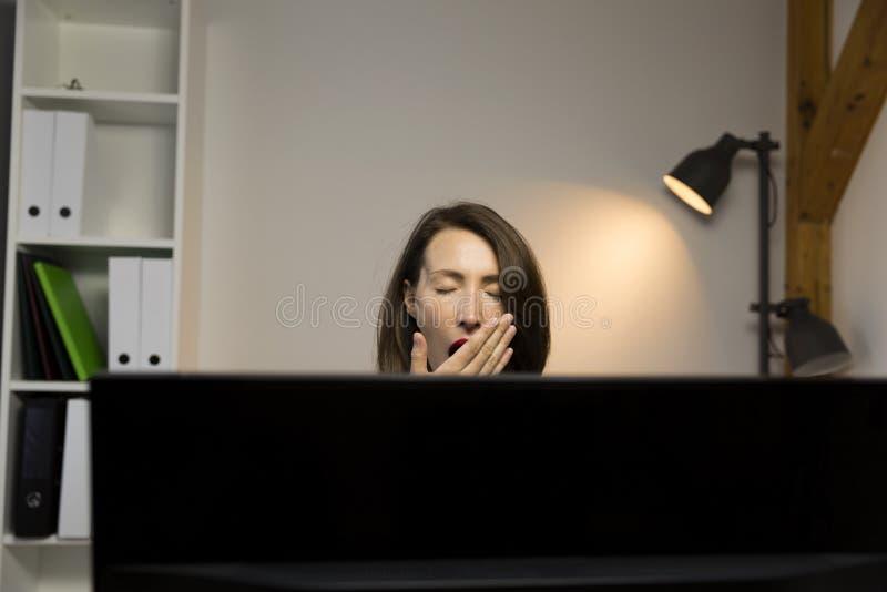 Jeune jolie femme fatiguée et épuisée du travail à côté de l'ordinateur image libre de droits