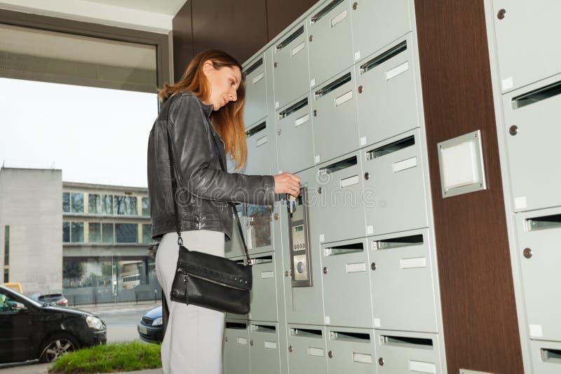 Jeune jolie femme fermant sa boîte aux lettres avec une clé photo stock
