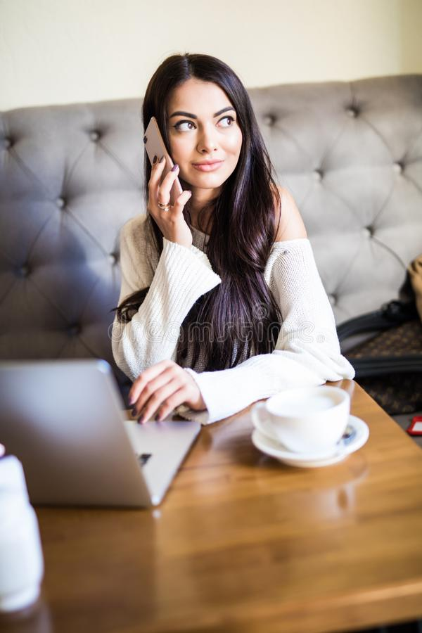 Jeune jolie femme parlant au t?l?phone avec un ordinateur portable sur la table en caf? image libre de droits