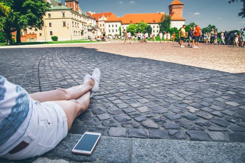 Jeune jolie femme s'asseyant au sol restting après longue promenade image libre de droits