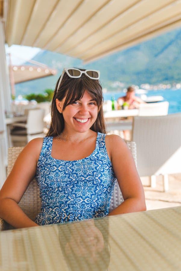 Jeune jolie femme s'asseyant en café au bord de la mer avec des montagnes sur le fond images stock