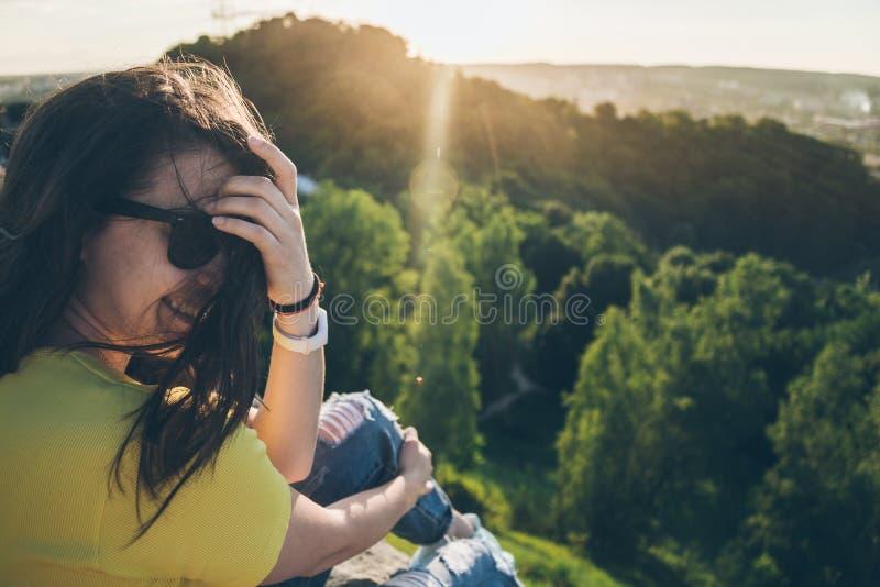Jeune jolie femme s'asseyant et souriant sur le dessus de la colline photo libre de droits