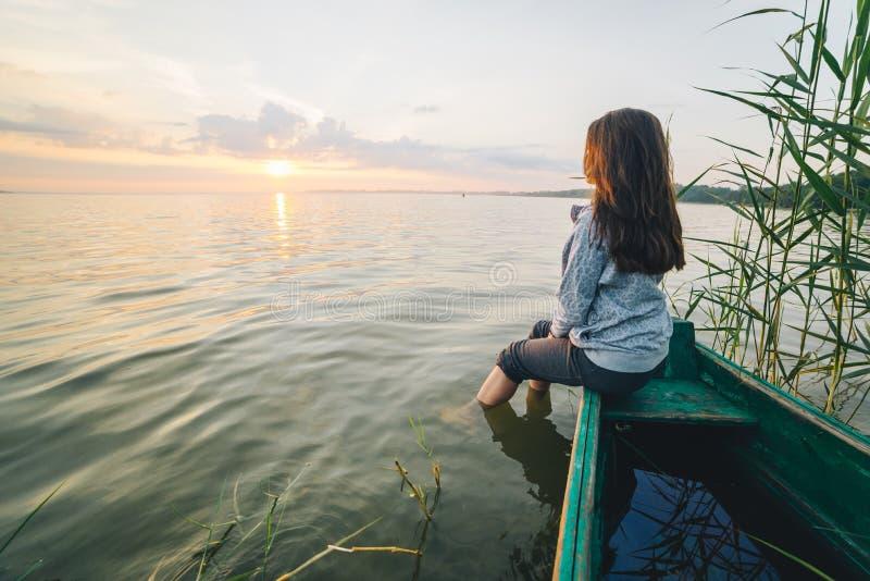 Jeune jolie femme s'asseyant sur le vieil accès et appréciant la vue du lever de soleil photographie stock libre de droits