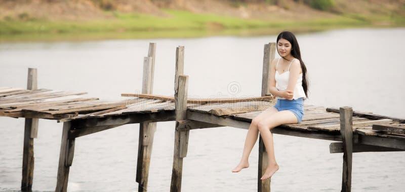 Jeune jolie femme seul s'asseyant image stock