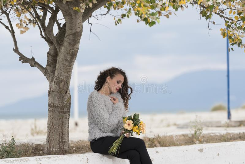 Jeune jolie femme tenant un bouquet des fleurs image libre de droits