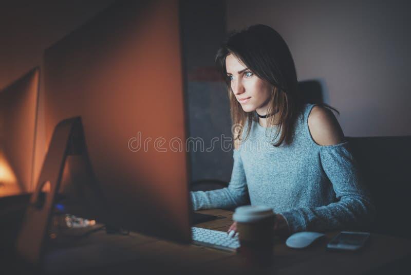 Jeune jolie femme travaillant au bureau moderne de studio la nuit
