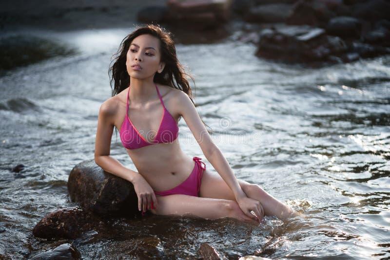 Jeune jolie fille asiatique maigre dans deux morceaux de maillot de bain rose détendre sur le bord de la mer photos libres de droits