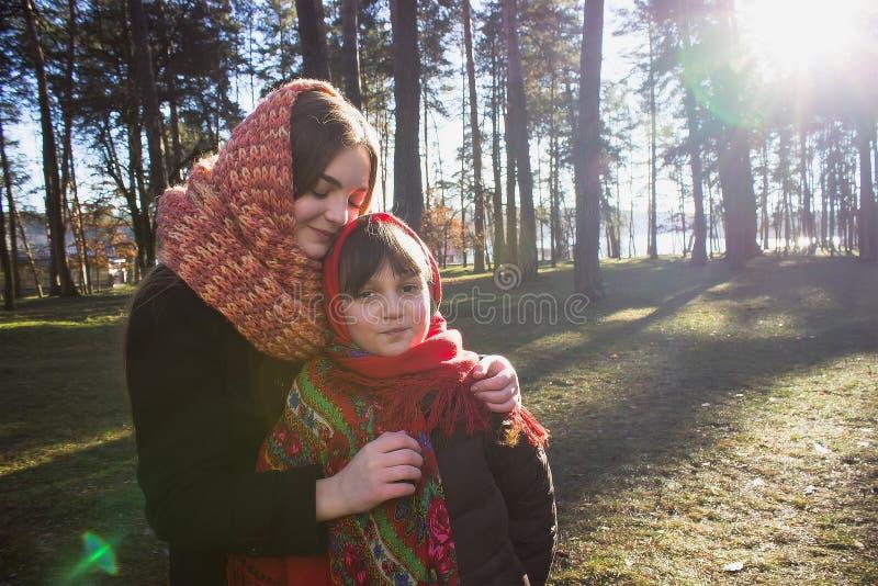 Jeune jolie fille avec une écharpe rouge sur sa forêt de tête au printemps images stock