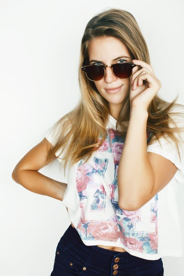 Jeune jolie fille blonde de l'adolescence posant gai d'isolement sur les lunettes de soleil de port de fond blanc, concept de per images libres de droits