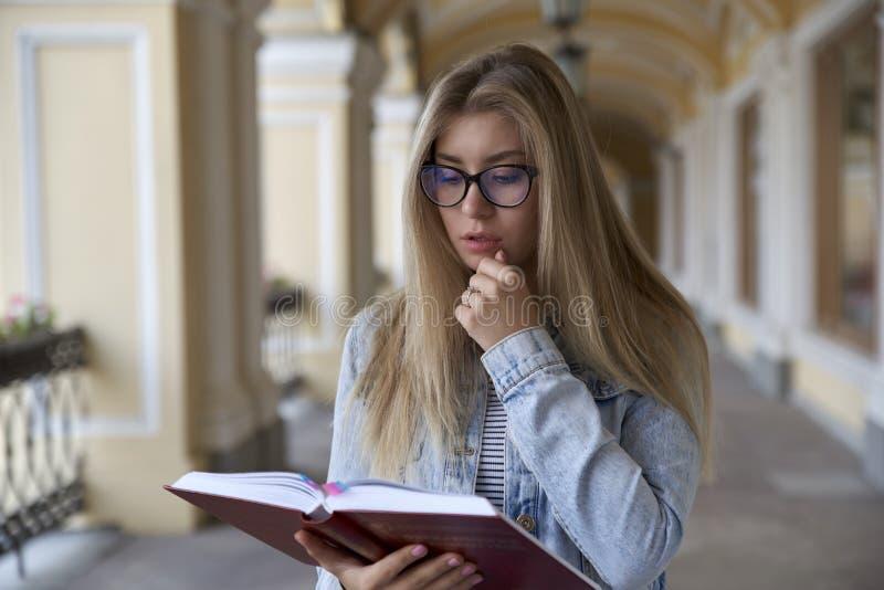 Jeune jolie fille d'étudiant avec de longs cheveux lisant pensivement a images stock