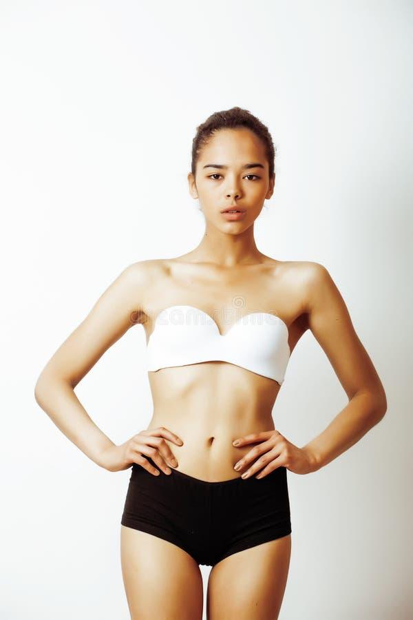 Jeune jolie fille d'afro-américain dans des sous-vêtements de sport posant sur le fond blanc, mulâtre de desserrage très mince de photographie stock libre de droits