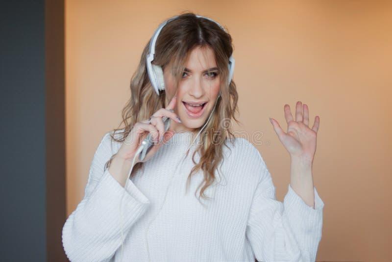 Jeune jolie fille dans des écouteurs avec le téléphone Écoutant la musique, la danse et le chant, à l'intérieur images libres de droits
