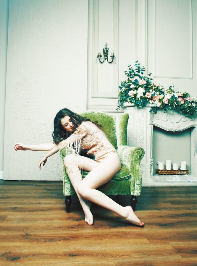 Jeune jolie fille de brune dans la robe de mode sur le sofa posant dans le lu photographie stock