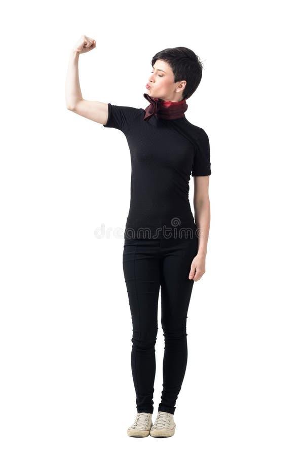 Jeune jolie fille de brune de cheveux courts fléchissant le muscle de bras de biceps photos libres de droits