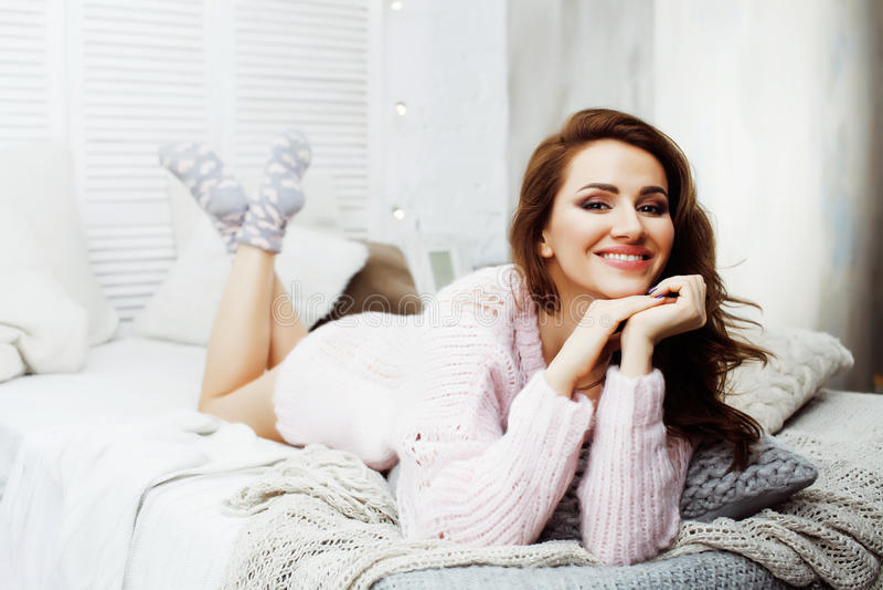 Jeune jolie fille de brune s'étendant dans le lit confortable avec le sourire heureux de port de chandail d'hiver de laine de caf photos libres de droits