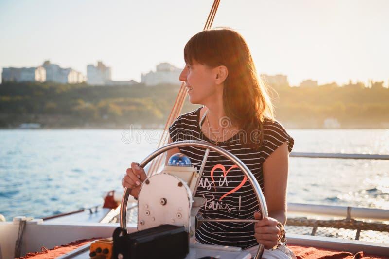 Jeune jolie fille de sourire dans la chemise rayée et les shorts blancs conduisant le yacht de luxe en mer, jour d'été chaud, cou photos stock