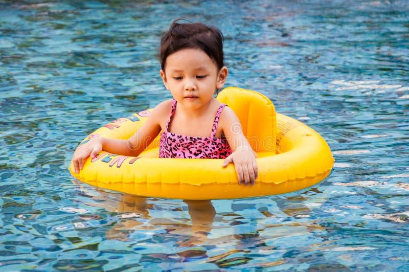 Jeune jolie fille en anneau jaune de natation dans la piscine avec le wat clair images stock