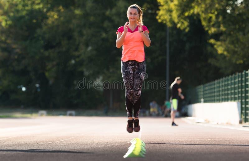 Jeune jolie fille faisant des exercices au champ de sport image libre de droits