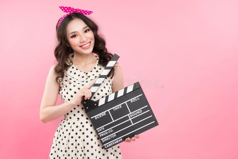 Jeune jolie fille mignonne étonnante tenant le panneau de clapet au-dessus de b rose image stock