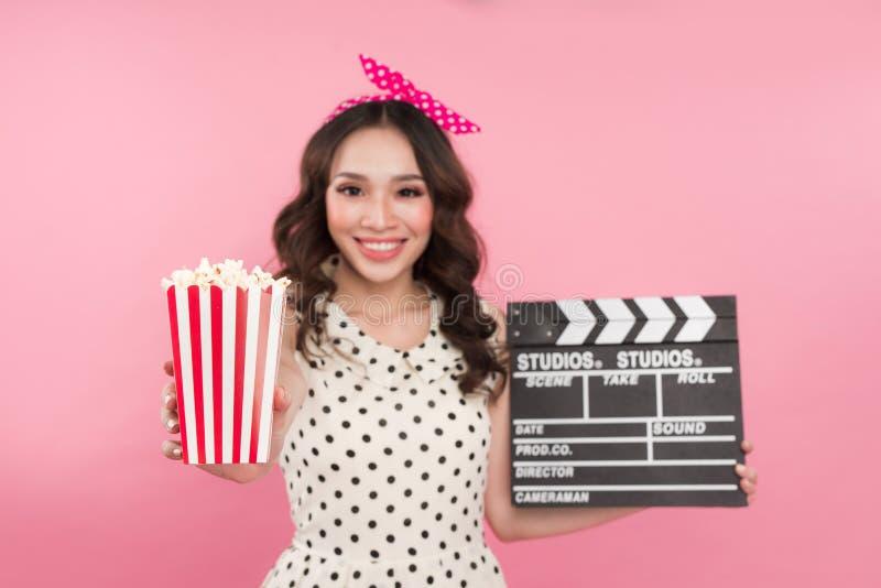 Jeune jolie fille mignonne étonnante tenant le panneau et la représentation de clapet photographie stock libre de droits