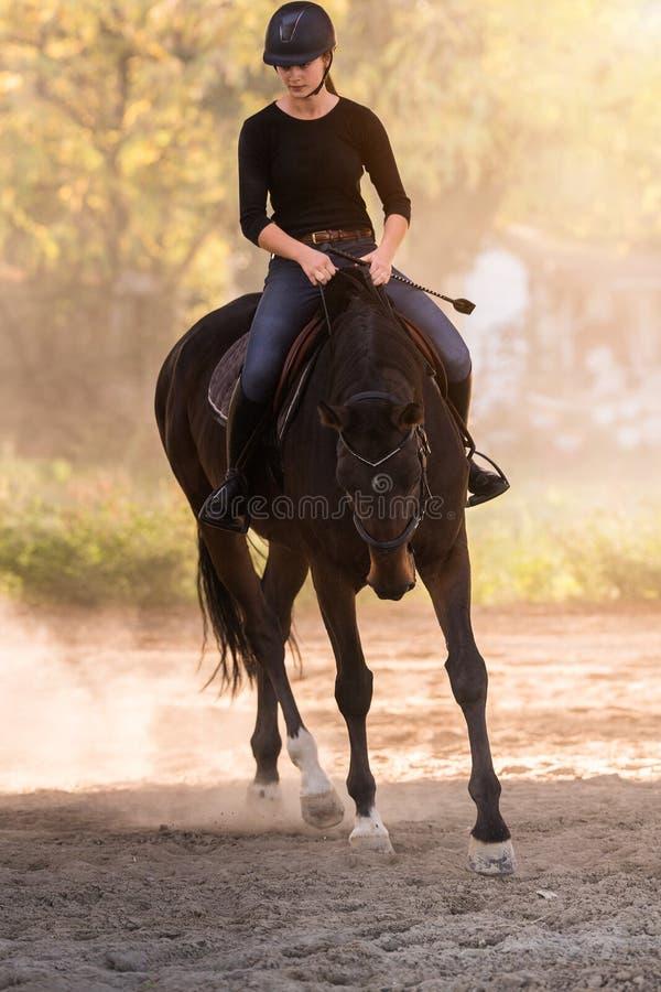 Jeune jolie fille montant un cheval avec les feuilles rétro-éclairées derrière photo stock