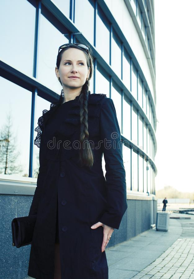 Jeune jolie fille près du bâtiment d'affaires marchant, femme d'affaires sur l'extérieur bleu image libre de droits