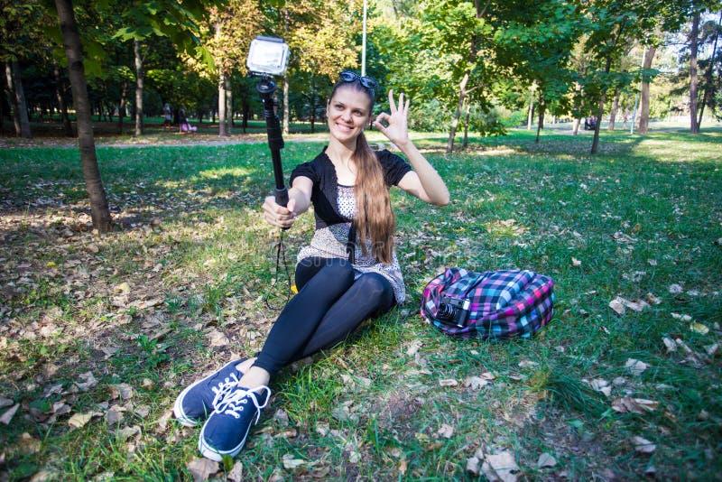 Jeune jolie fille s'asseyant sur l'herbe et prenant le selfie sur un appareil-photo d'action photographie stock